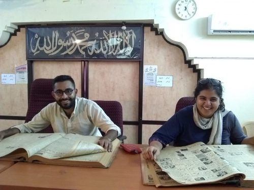 Aman Madan and Vanshika HUL Intern sit with two open, bound volumes of newspapers.