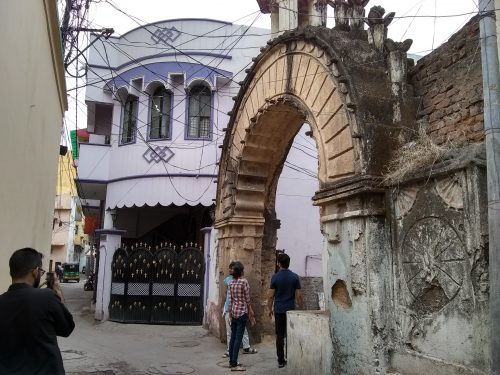 Aman and HUL Interns observing Old City Architecture. There is a stone archway and whitewashed, two-story building.