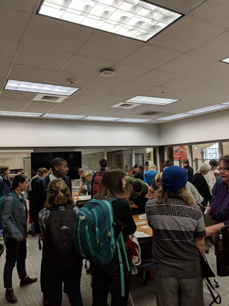 Image of students, townsfolk, and professors interacting with archival materials in the fishbowl as part of the Davidson Disorientation Tour in 2018.