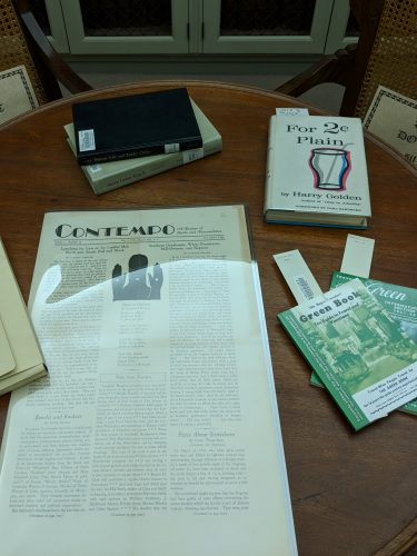 Green Books, Contempo magazine, For 2 Cents Plain, and MLK publications arranged on a table for a Humanities course.